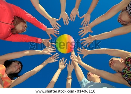 Several hands reaching out together in a circle for volley ball against blue sky - stock photo