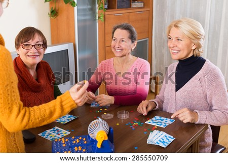 Several happy female pensioners playing board game at the home - stock photo