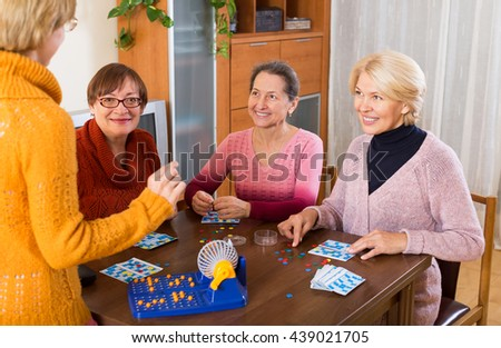 Several happy female pensioners playing board game in home