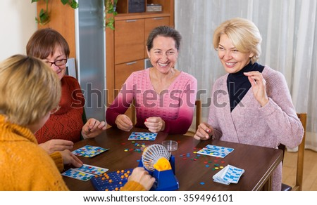Several happy female pensioners playing board game in room at the home - stock photo