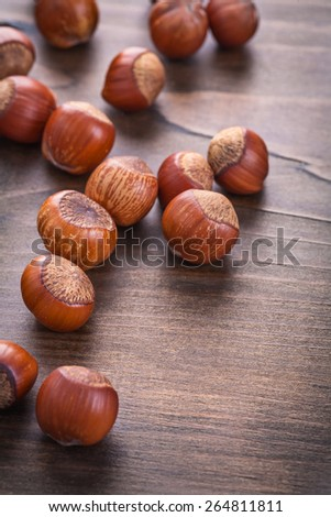 several hazelnuts on vintage wooden board food and drink concept  - stock photo