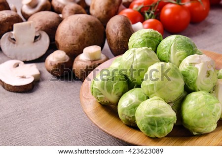 Several heads of fresh wet brussels sprouts on a wooden plate, mushrooms and cherry tomatoes on a linen fabric . - stock photo