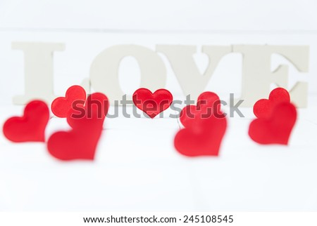 Several heart shapes and in the background wooden letters forming word love. Valentines Day background. Shallow depth of field - stock photo
