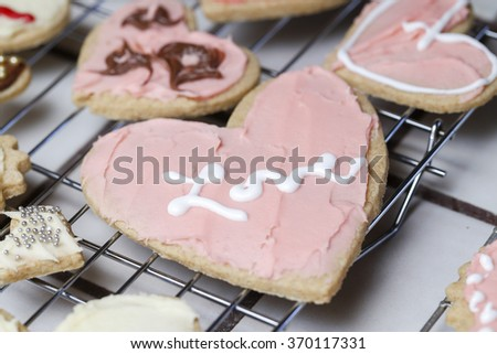 Several heart Valentine holiday cookies in pink frosting with one with the name Love written in white frosting  in cursive. - stock photo