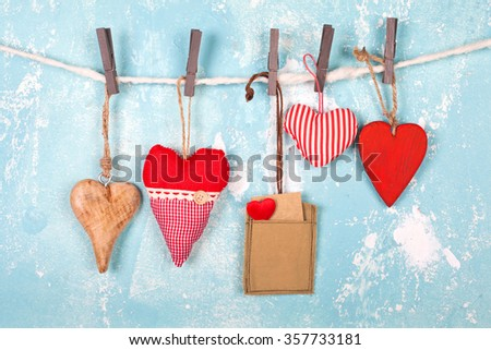 several hearts with a tag over blue wall, valentines love background - stock photo