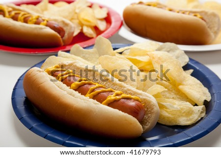 Several hot dogs on colored plates on a gingham background - stock photo