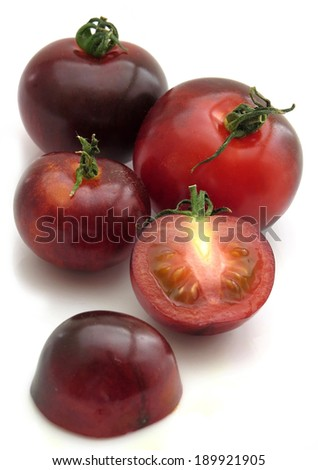 Several Indigo rose tomatoes, one chopped open - stock photo