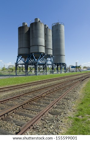 several industrial processing tanks for the chemical industry next to a railroad - stock photo
