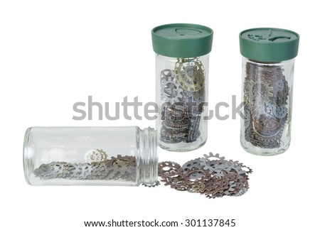 Several jars full of various gears with interlinking teeth and cogs - path included - stock photo