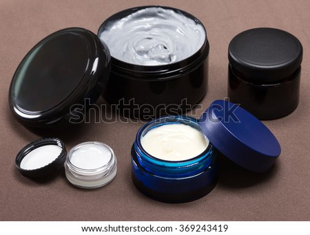 Several jars of different sizes filled with creams on brown background. Various skin care cosmetic products. Cosmetics with natural ingredients. Skincare for men - stock photo