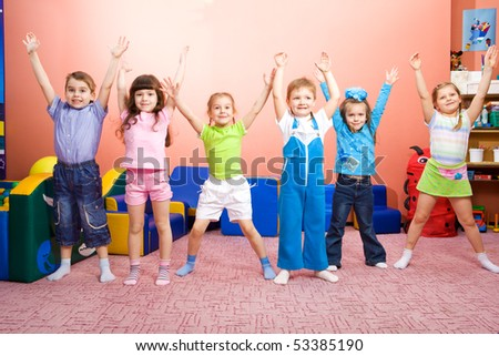 Several joyful kids with their hands up