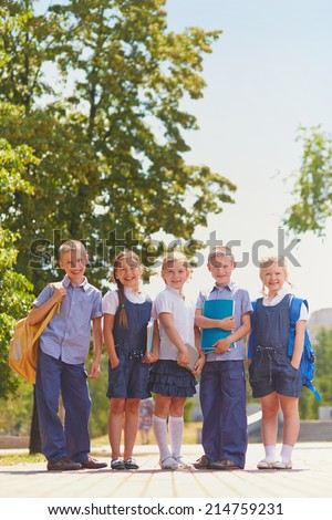 Several kids in school uniform posing for camera in park - stock photo