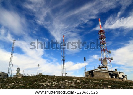 Several kind of communication antennas and a red and white tower against deep mountain blue sky with white clouds - stock photo