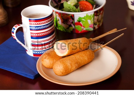 several korndogov on a plate, salad, pistachio, coffee - stock photo