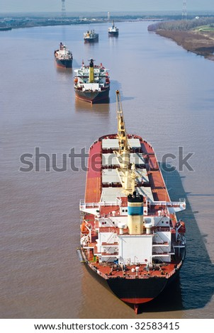 Several large cargo ships on the Mississippi River - stock photo