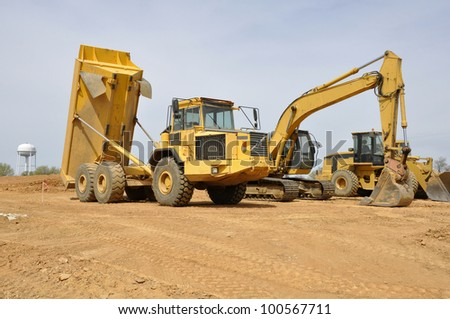 several large construction vehicles, including a dump truck and backhoe - stock photo