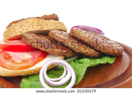 several large hamburger with loaf on wooden plate isolated over white background - stock photo