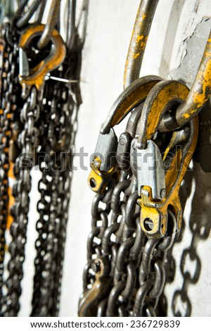Several large industrial weathered yellow hooks attached to chain and a pulley. - stock photo