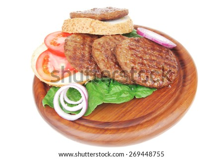 several large roast hamburger with loaf on wooden plate isolated over white background - stock photo