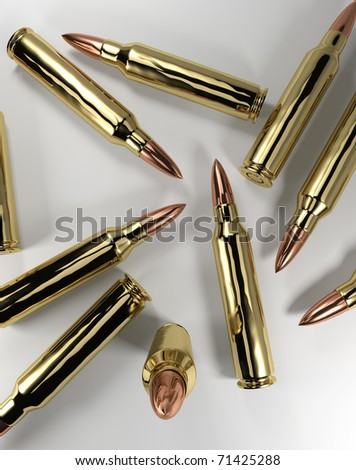 Several 5.56mm rifle bullets spread out. - stock photo