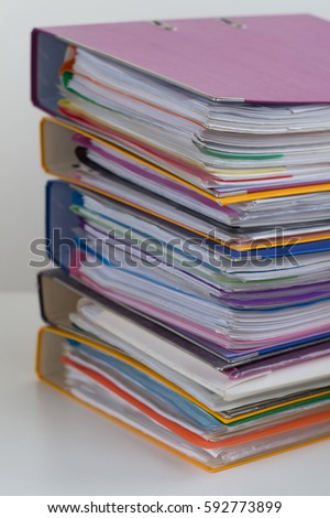 Several multicolored folders with documents stacked in a pile on