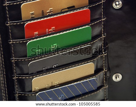 Several Multicolored  red green black  blue gold credit cards in the black wallet. - stock photo