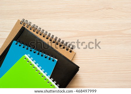 Several notebooks and notepads at office desk. Top view with copy space.