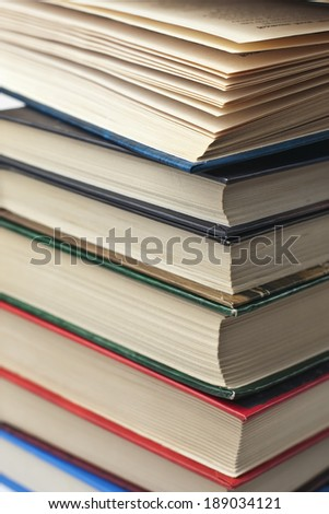 several old dusty books stacked in a pile - stock photo