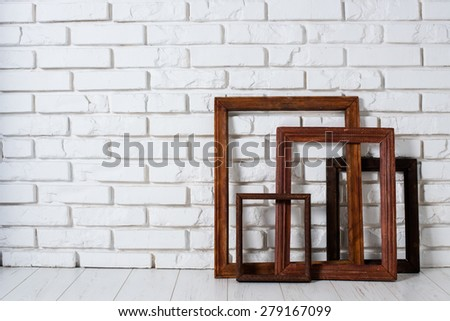 Several old empty wooden frames on a  white brick wall background, room interior. - stock photo