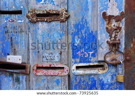 Several old mailboxes in a n old wooden door painted blue - stock photo