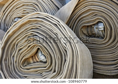Several old rolled fire hoses with nozzles close-up - stock photo