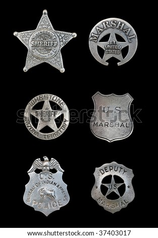 Several old, vintage sheriff, marshall, and police badges isolated over black - stock photo