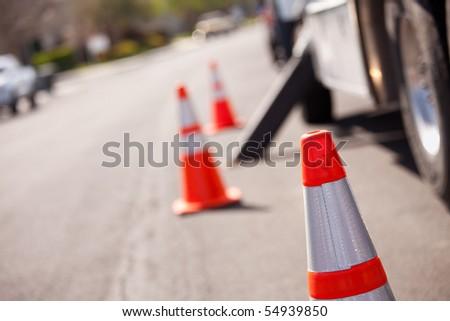 Several Orange Hazard Cones and Utility Truck in Street. - stock photo