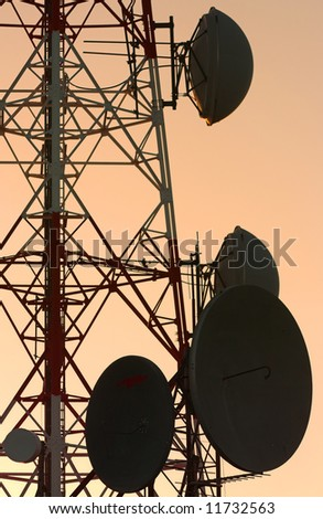 Several parabolic antennas, first rays of the morning sun - stock photo