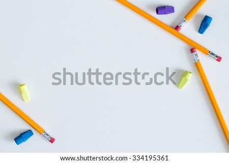 Several pencils and erasers placed in a pleasing way on white paper to create a border for multiple purposes. This can be used as a horizontal or vertical format or it can even be flipped and rotated. - stock photo