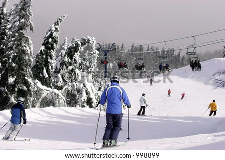 Several People are Skiing Downhill - stock photo