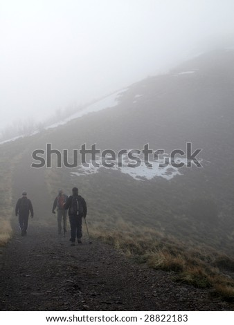 Several people climbing along rocky ridge on a trail in the fog
