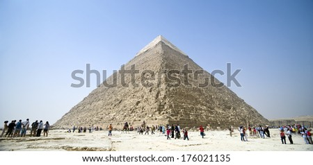 Several people gathering in front of a pyramid. - stock photo