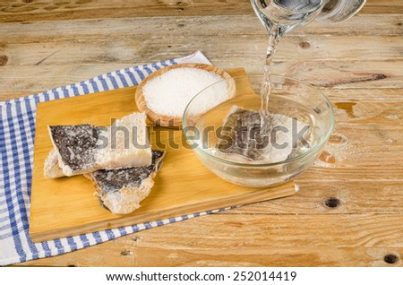 Several pieces of dried cod being desalted in fresh water - stock photo