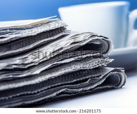 Several pieces of newspaper on a table with a cup of coffee in the background - stock photo