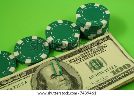 several piles of gambling chips beside bills of one hundred dollars