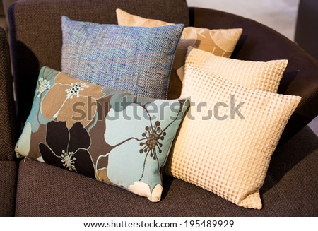 several pillows on a brown sofa - stock photo