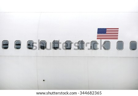 Several plane windows with the American flag - stock photo