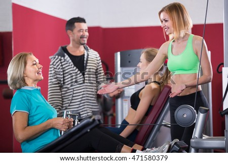 Several positive women and man having workout on machines in gym. Focus on woman