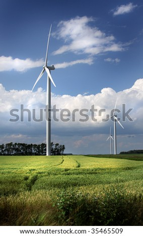 Several power-generating windmills in a field. - stock photo