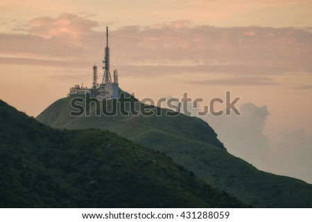 Several radio towers with sunrise sky in background - stock photo