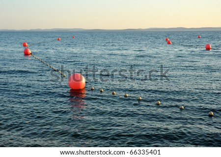 several red buoys on calm sea water, coastline in distance - stock photo