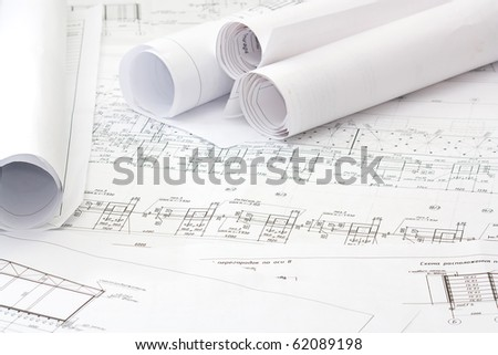 Several rolls of blueprints on an open blueprint - stock photo