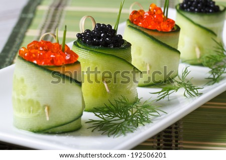Several rolls of fresh cucumbers with red and black caviar on a white plate closeup horizontal  - stock photo