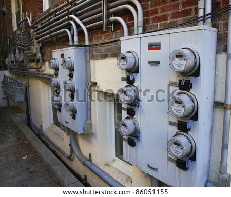 Several rows of electric and gas meters on the side of a brick apartment